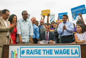 <em>Los Angeles Mayor Eric Garcetti, center, joins members of the City Council and community leaders as he signs into law an ordinance that will gradually raise the minimum wage to $15 an hour by 2020, in at Martin Luther King Jr. Park in Los Angeles, Saturday, June 13, 2015. The ordinance makes Los Angeles the largest city in the U.S. to gradually raise the minimum wage to $15 an hour.</em> (AP Photo/Ringo H.W. Chiu)