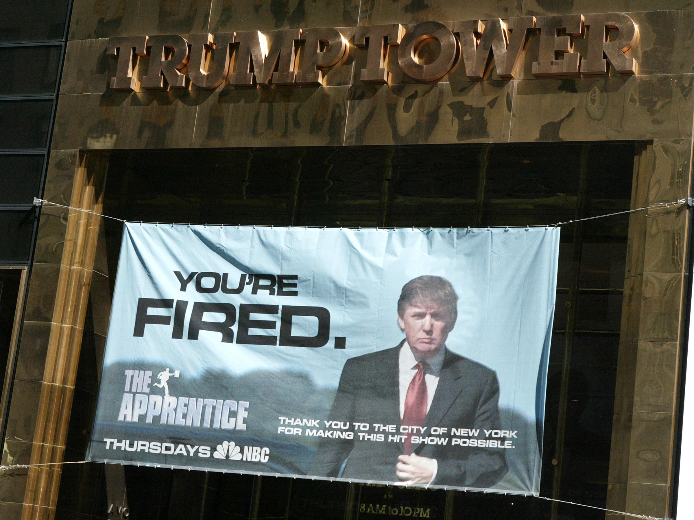 A sign advertising Trump's television show The Apprentice hangs at Trump Towers in New York City in 2004. Courtesy NBC
